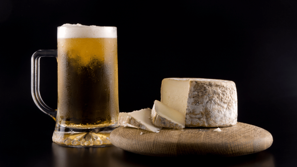 A pint of cold beer with a block of cheese on a wooden serving board against a black background
