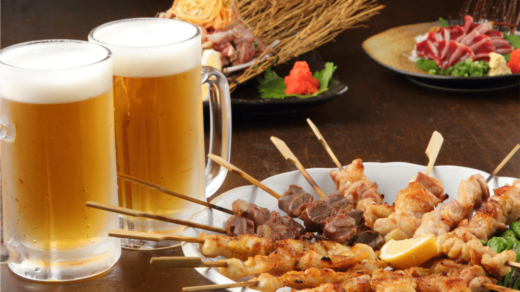 two glasses of beer surrounded by skewers of grilled meat