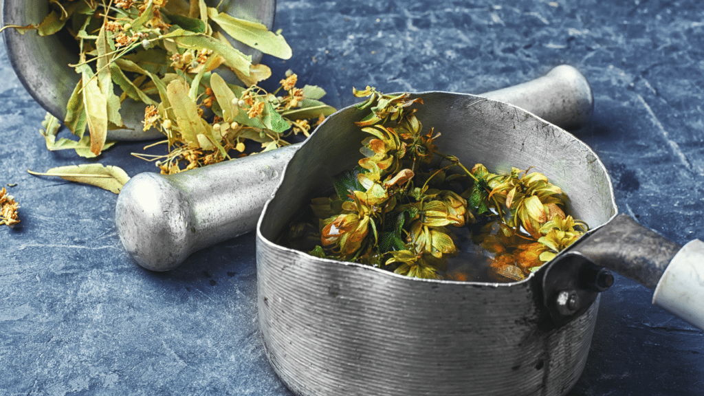 Hops in a pot with a pestle beside