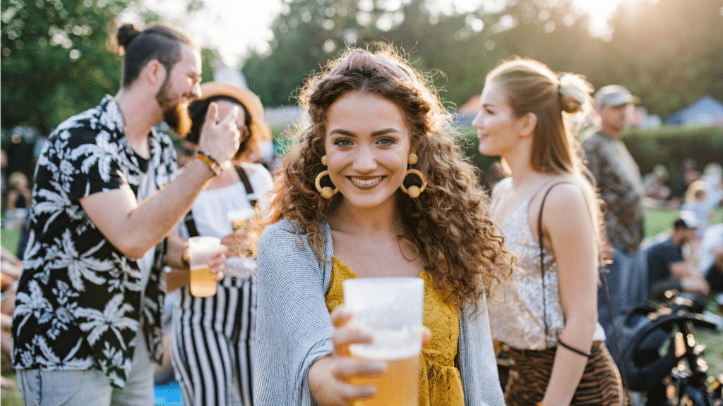 Girl holding beer out to the camera with people drinking beer in the background